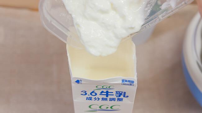 種菌のブルガリアヨーグルト100gを牛乳パックに投入している