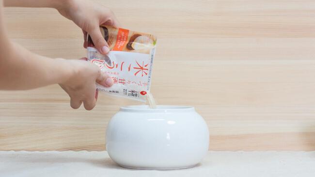 陶器容器に米麹を入れている