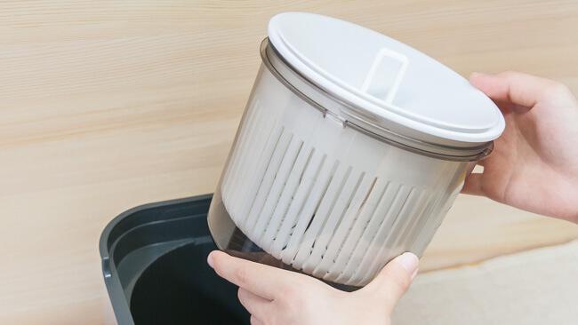 本体に入っている納豆容器セットを取り出している