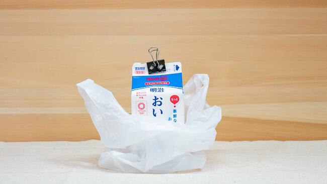 牛乳パックをビニール袋に入れている
