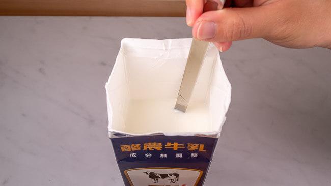 牛乳パックの中でR1ヨーグルトと牛乳をかき混ぜている