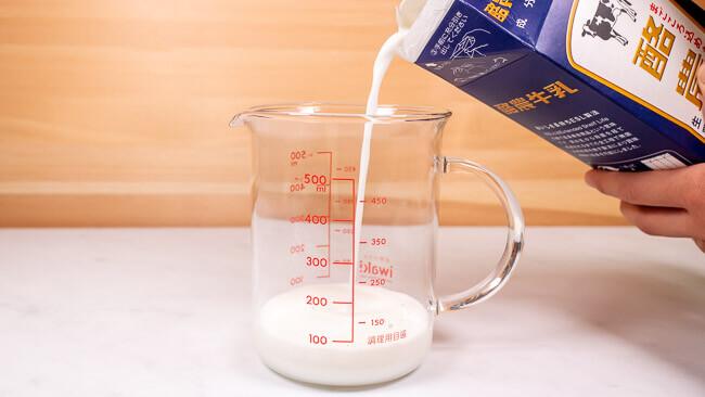 約100mlの牛乳を計量カップに移している