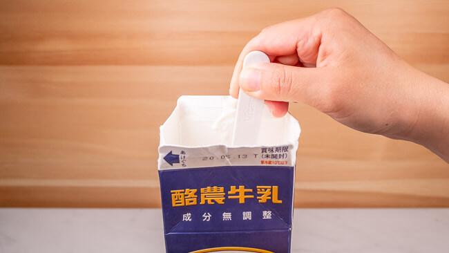 付属のヨーグルトスプーンで牛乳パック内の牛乳とR1ヨーグルトをかき混ぜている
